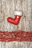 Red sock with garland on the old wood Royalty Free Stock Photography
