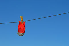 Red Sock On A Washing Line. A single red sock pegged on a washing line with a blue sky background Royalty Free Stock Photography