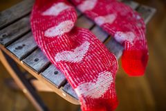 Red socks with heart pattern on wooden chair Royalty Free Stock Image