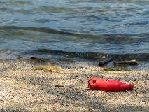 Red soda bottles that were left by tourists on the beach royalty free stock photos