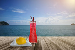 Red soda and orange sponge cake on Wooden table front of blurred background. Perspective brown wood over blur sea and blue sky Stock Photos