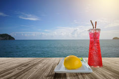 Red soda and sponge cake with orange Marmalade jam on Wooden table front of blurred sea background Stock Photography