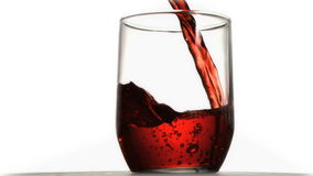 Red soda in super slow motion flowing in a glass. Against a white background stock video