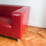 Red sofa. In a room with oak parquet fllor and white walls Stock Images