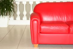Red Sofa. Red leather sofa,tile flooring and a white railing in a modern home Stock Photo