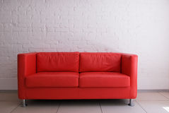 Red sofa and brick wall Stock Images