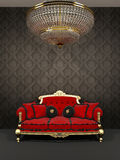 Red sofa and chandelier in royal interior Royalty Free Stock Image