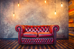 Red sofa couch. In vintage room with lamps royalty free stock photo