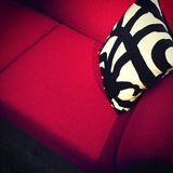Red sofa with decorative cushion Stock Images