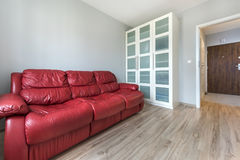 Red sofa in empty room Stock Images