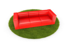 Red sofa on green field Stock Photo