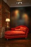 Red sofa and lamp. Beautiful red sofa and lamp at a wall from a brick Royalty Free Stock Image