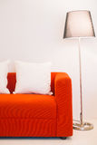 Red sofa with pillow and light lamp Stock Photography
