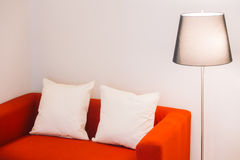 Red sofa with pillow and light lamp Stock Images