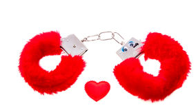 Red soft sexual handcuffs. With a heart isolated over white Stock Image