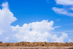 Red soil with blue sky and white clouds. Royalty Free Stock Image