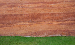Red soil wall background and green grass field Royalty Free Stock Images