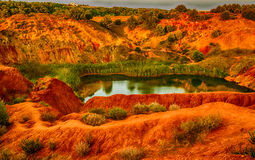 Red soils around the lake in bauxite quarry Stock Photos
