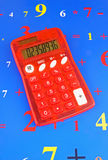 Red solar calculator. Red solar powered electronic calculator on page of numbers in various sizes and colors Royalty Free Stock Image