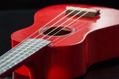 Red soprano Ukulele. Detail of the body and the keyboard of a soprano ukulele Royalty Free Stock Image