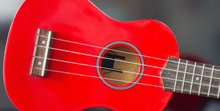Red Soprano Ukulele. Detail of the body and the keyboard of a soprano red ukulele royalty free stock photo