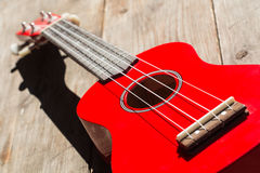 Red soprano ukulele. Detail of the body and the keyboard of a red soprano ukulele Stock Photography
