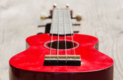 Red soprano ukulele. Detail of the body and the keyboard of a red soprano ukulele royalty free stock photography