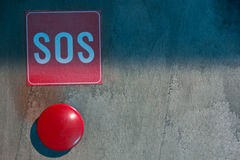 The red SOS button on a gray background. Red panic button on a concrete wall royalty free stock image