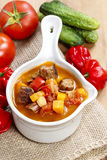 Red soup with vegetables and meat. Fresh vegetables around Stock Photos