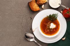 Red soup in a white plate on a gray background, top view. Royalty Free Stock Photography