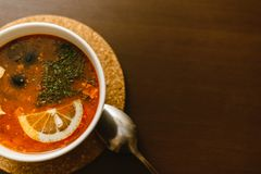 Red soup on wooden background. Borscht, solyanka with lemon, olives and sour cream on a brown table stock image