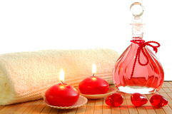 Red spa. Decoration with massage oil bottle and candles Royalty Free Stock Image