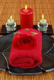 Red Spa. Towel, rose, and aromatic candles on bamboo Royalty Free Stock Image