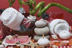 Red spa background. Some hygiene items, candles and a bamboo branch on a red bamboo mat Stock Photos