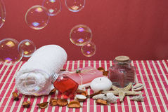 Red spa with bubbles. Red spa background with bubbles and some hygiene items on a red bamboo mat Stock Photography