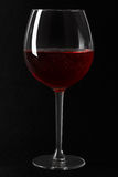 Red sparkling wine glass on black background. Clipping path included Royalty Free Stock Image