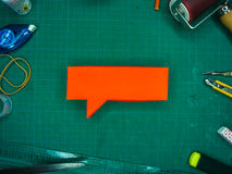Red Speech Bubble on Green Cutting Mat, with various tools, shot Stock Photography
