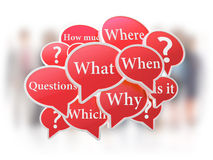 Red speech bubbles with questions. On white background with blur peolpe Royalty Free Stock Photography