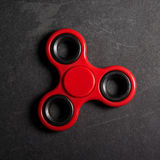 Red spinner Fidget finger stress anxiety relief toy. Stock Photo
