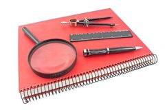Red spiral notebook with drawing compass, ruler and magnifier is Royalty Free Stock Images