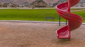 Red spiral slide with mountain homes and lawn view stock photo