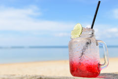 Red spirit drink lemon soda cocktail on beach. Red spirit drink lemon soda cocktail on the beach stock photo