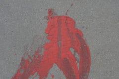 Red splash on grey asphalt pavement royalty free stock image