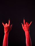 Red spooky hands showing heavy metal gesture Stock Images