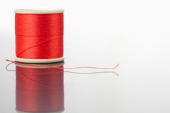 Red spool of thread on a table Royalty Free Stock Photo