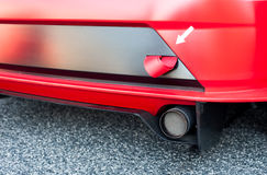 Red sport car bumper and ribbon detail. Red sport car bumper, tube and white arrow pointing to ribbon detail Royalty Free Stock Photo