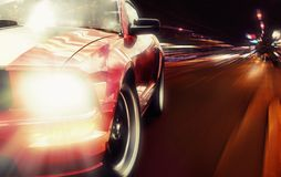 Red sport car. Closeup picture on a narrow night road Stock Photo
