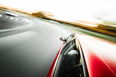 Red sport car driving during day Royalty Free Stock Image