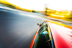 Red sport car driving during day Stock Photo