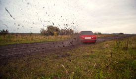 Red sport car driving on the mud Stock Photo